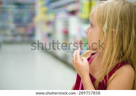 Adorable girl select goods in supermarket - stock photo