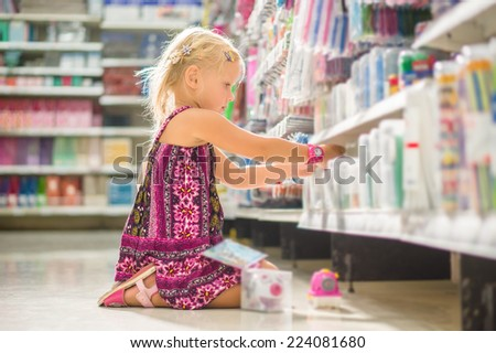 Adorable girl select pencil sharpener in stationery department sitting on floor in supermarket - stock photo
