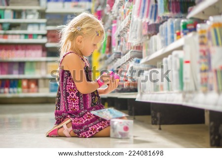 Adorable girl select pencil sharpener in stationery department sitting on floor in supermarket