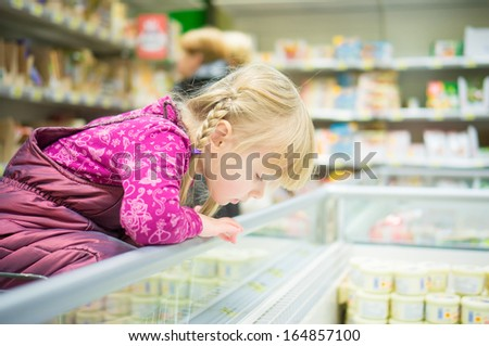 Adorable girl select products at fridge in supermarket - stock photo
