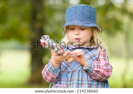 Adorable girl shoot with toy gun on playground