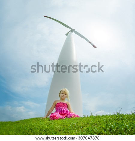 Adorable girl sit on grass with giant white wind turbine generating electricity on back - stock photo