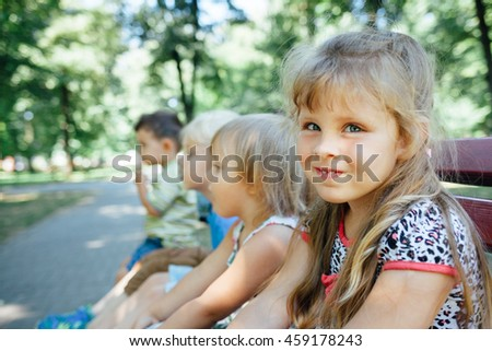 Adorable girl sits on a park bench with friends
