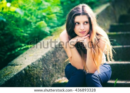 Adorable girl sitting on a stairs in a nature