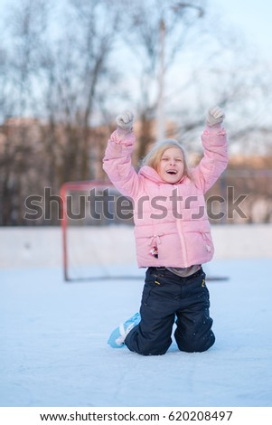 Adorable girl skates on ice ring on sunset in pink jacket applause victory