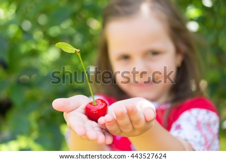 Adorable girl smiling and holding in her palms a fresh cherry on a beautiful summer day - stock photo