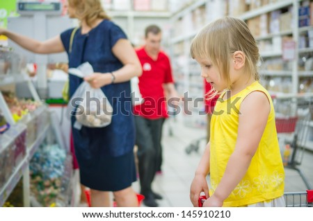 Adorable girl stay in shopping cart and select candies - stock photo