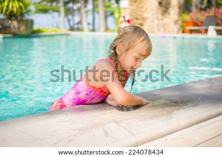 Adorable girl stay in water at side of swimming pool in tropical beach resort - stock photo