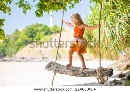 Adorable girl stay on rope swing under palm trees on tropical island - stock photo