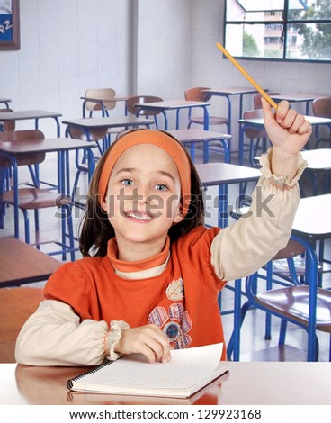 Adorable girl student asking to speak in her school class - stock photo