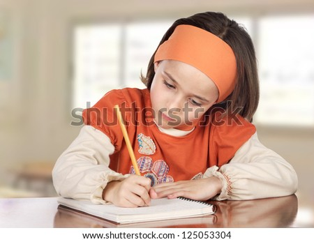 Adorable girl studying in the school with a window of background
