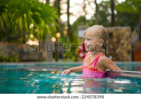 Adorable girl swim in pool at tropical beach resort . Stay at metal pool divider border - stock photo