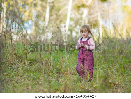 Adorable girl walk by the road in autumn park