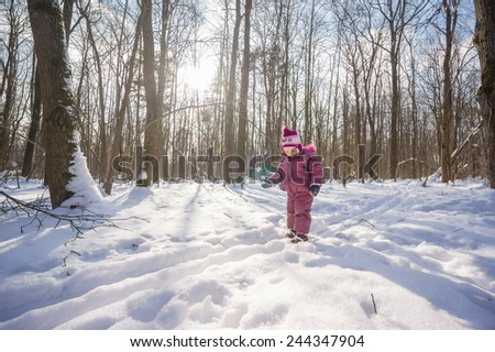 Adorable girl walk on ski in park by ski tracks - stock photo