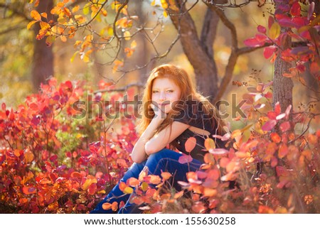 Adorable girl with autumn leaves in park