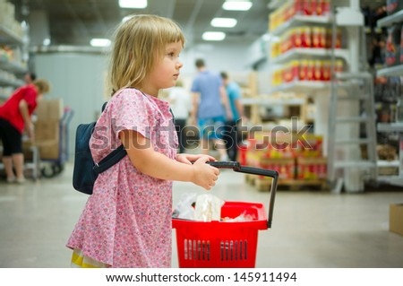 Adorable girl with backpack stay with red shopping cart in supermarket