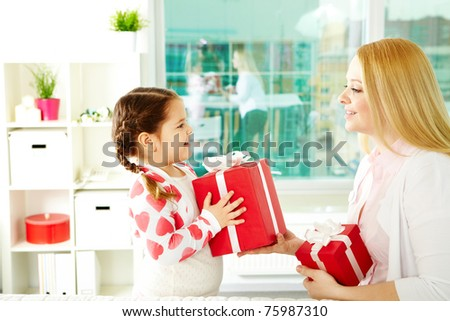 Adorable girl with big giftbox giving it to her mother - stock photo