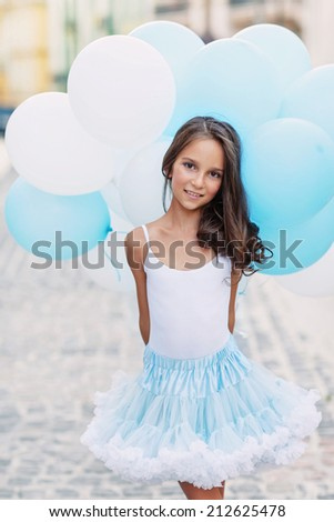 Adorable girl with blue and white balloons - stock photo