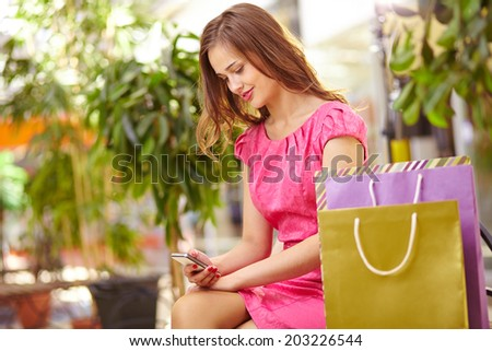 Adorable girl with cellphone sitting in the mall with shopping bags near by - stock photo