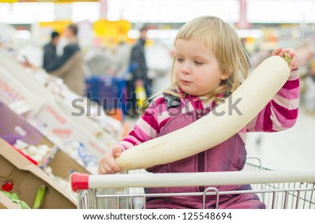 Adorable girl with daikon radish in shopping cart in supermarket