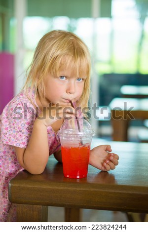 Adorable girl with iced lemonade glass with straw in restaurant