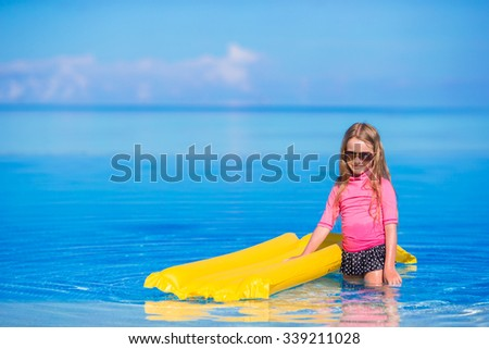 Adorable girl with inflatable air mattress in outdoor swimming pool - stock photo