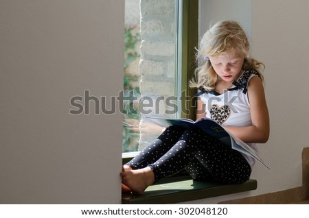 adorable girl with long blond hair sitting in the window table with book - stock photo