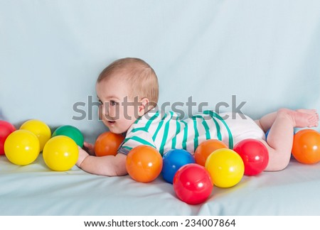 Adorable happy baby boy with multicolored balls on blue background - stock photo