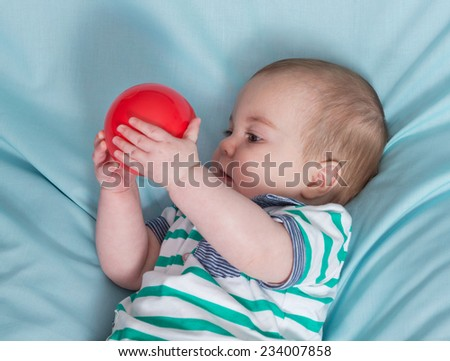 Adorable happy baby boy with red ball on blue background