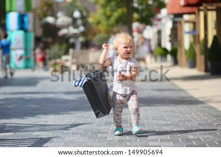 Adorable happy baby girl walking on the street in the middle of the city during sales carrying black shopping bag in her hand. Crowd of people in the background. - stock photo