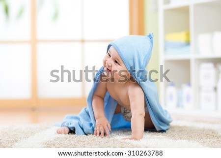 Adorable happy baby in towel crawling on floor at home - stock photo
