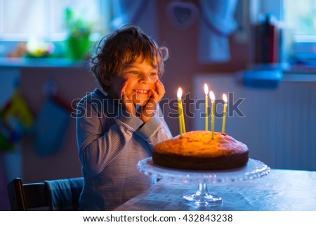 Adorable happy blond little kid boy celebrating his birthday. Child blowing candles on homemade baked cake, indoor. Birthday party for children. - stock photo
