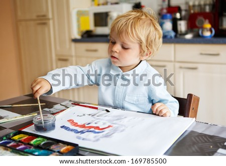Adorable happy boy of two years drawing with paints - stock photo
