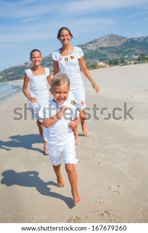 Adorable happy boy with his sisters running on beach vacation