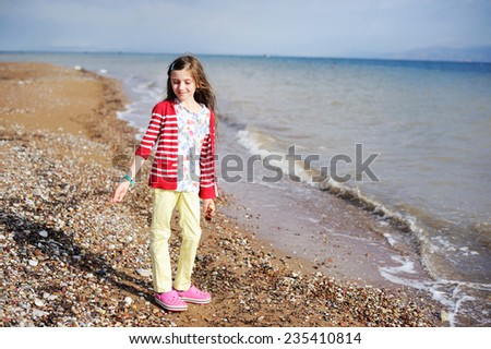 Adorable happy brunette young girl on beach vacation in the stormy day - stock photo