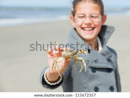 Adorable happy girl holding crab on the beach on spring day. Focus on the crab.