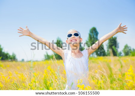 Adorable happy girl in glasses in flowers yellow field. Summer freedom andjoy concept. - stock photo