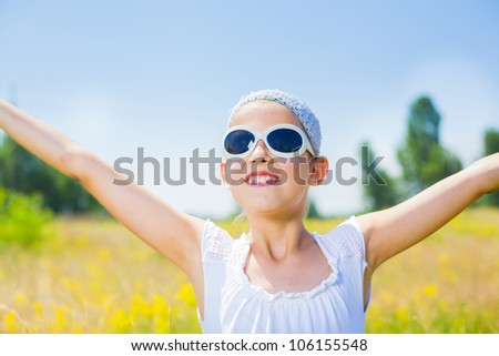 Adorable happy girl in glasses in flowers yellow field. Summer freedom andjoy concept.