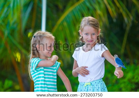 Adorable happy girls at beach with colorful little bird - stock photo
