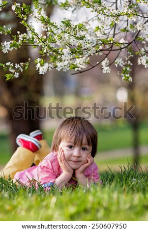 Adorable happy kid outdoors on spring day in beautiful blooming garden - stock photo