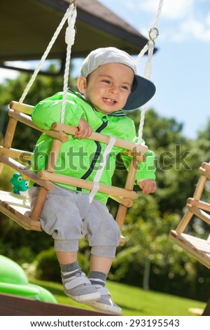 Adorable happy kid swinging outdoors