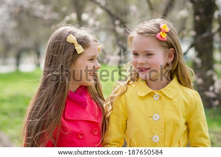Adorable happy kids outdoors on spring day in beautiful blooming garden. - stock photo
