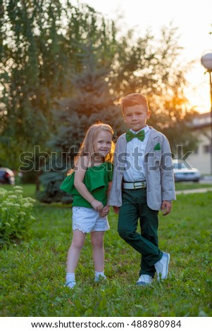 Adorable happy kids outdoors on sunset. Funny beautiful couple. beauty little girl and boy together.