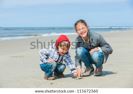 Adorable happy kids plaing with crab on the beach on spring day - stock photo