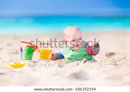 Adorable happy laughing little baby boy in a colorful sun protection suit playing with  toy buckets and plastic shovel digging in sand on a beautiful exotic tropical beach with turquoise water