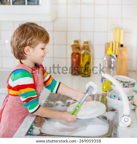 Adorable happy little blond kid boy washing dishes in domestic kitchen. Child having fun with helping his parents with housework. Indoors, kid in colorful clothes.