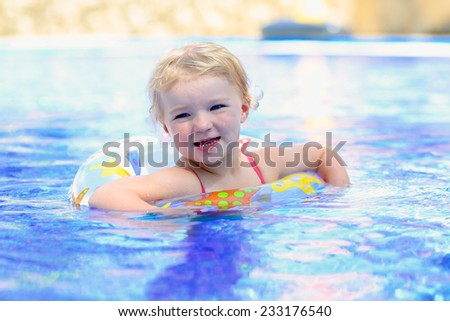 Adorable happy little child, curly toddler girl in swimming suit having fun relaxing and floating on an inflatable toy ring in a pool on sunny day during summer vacation in resort