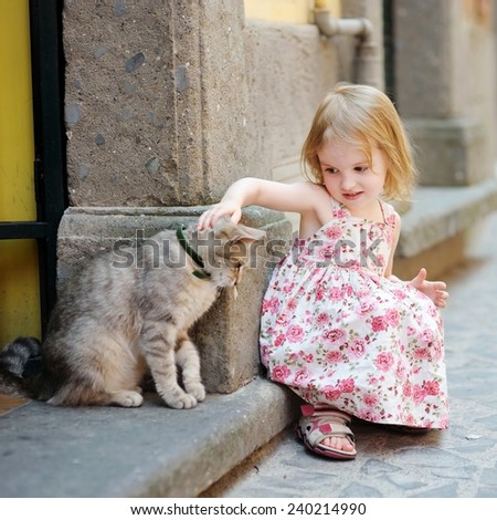 Adorable happy little girl and a cat outdoors - stock photo