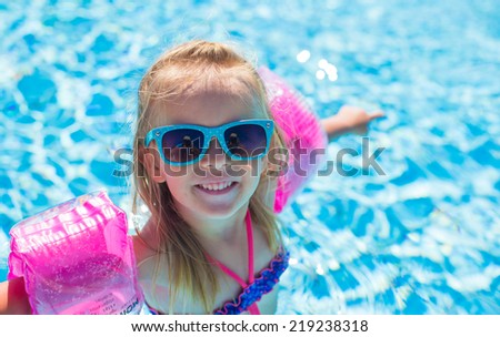 Adorable happy little girl have fun in the swimming pool - stock photo