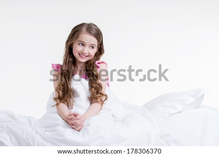 Adorable happy little girl in pink nightie awake and sitting on the bed - isolated on white. - stock photo